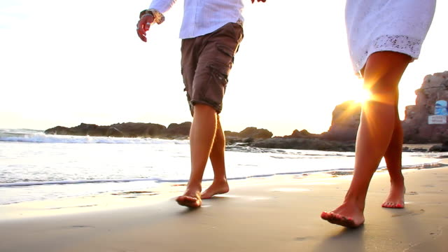 Older couple walks the beach barefoot in Mexico during sunset video
