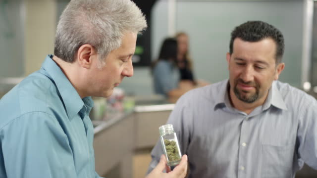 Older customer at marijuana shop looking closely at product, smelling it video