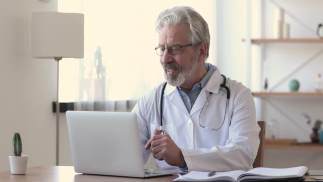 пожилой врач разговаривает с пациентом, делая видеозвонок на ноутбуке - дистанционный стоковые видео и кадры b-roll