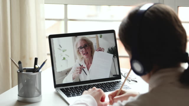 Older female online teacher giving distance lesson on laptop screen Older female online teacher coach gives web class, distance lesson, professional course, teaching remote student wearing headphones watching webinar or video calling. Over shoulder laptop screen view adult stock videos & royalty-free footage