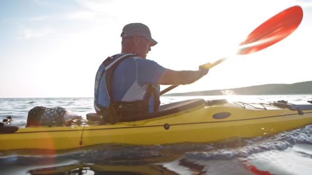SLO MO Older male kayaker paddling his sea kayak in the sun