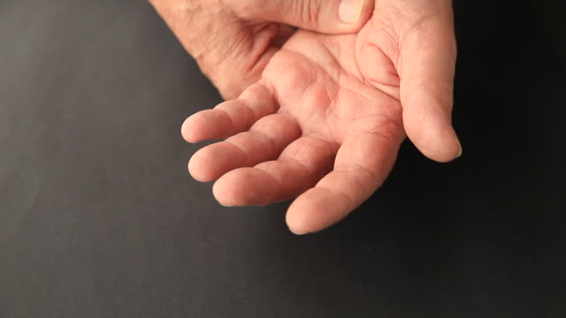 Older man has finger tremors Overhead of senior man with involuntary movements in his hands shivering stock videos & royalty-free footage