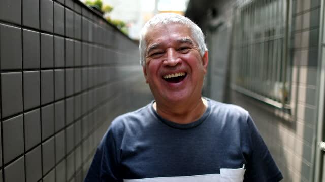 пожилой человек портрет улыбается и смеется, радостный 60-летний старший глядя на камеру, случайные - white background стоковые видео и кадры b-roll