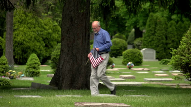 stockvideo's en b-roll-footage met older man putting us flag in a grave - funeral crying