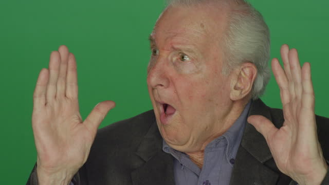 Older man reacts in shock, on a green screen studio background video