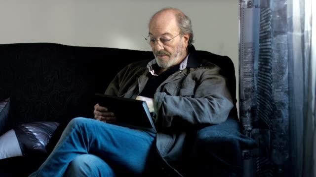 Older man reading on tablet pc video