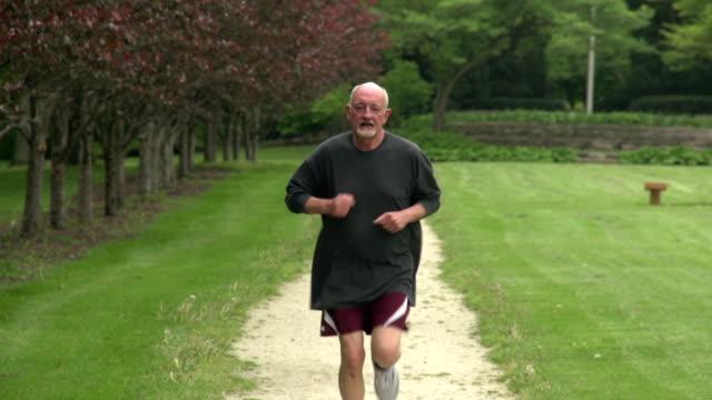 Older man running towards camera in slow motion video