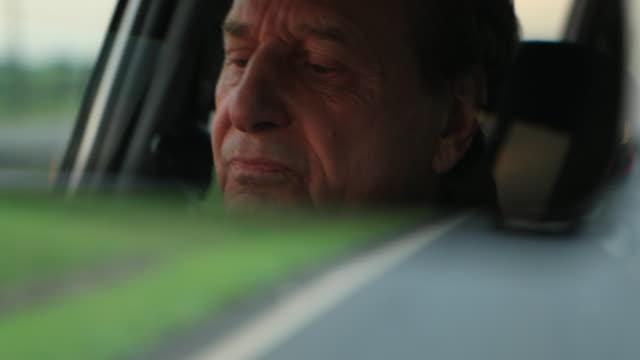 vídeos de stock e filmes b-roll de older man seen through rearview mirror while driving on road in 4k - old men window