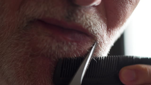 older man trimming his moustache during quarantine isolation - baffo peluria del viso video stock e b–roll