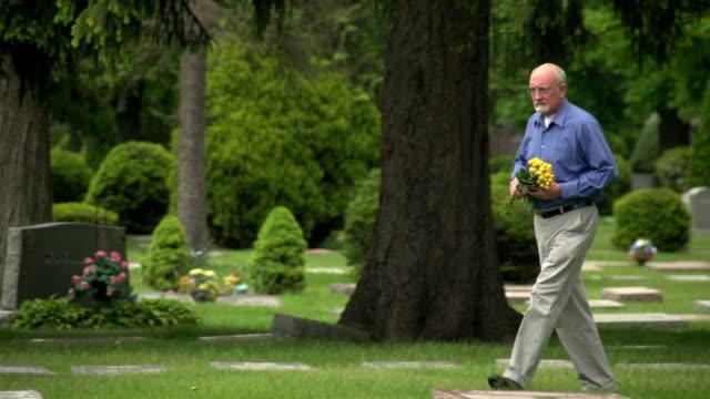 older man walking through cemetery holding flowers - ljus på grav bildbanksvideor och videomaterial från bakom kulisserna