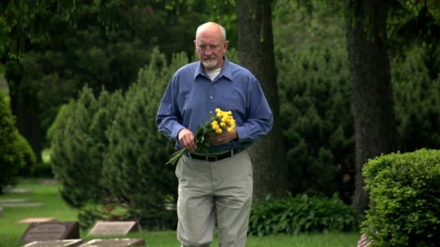 older man walking through cemetery holding flowers - minnesmärke bildbanksvideor och videomaterial från bakom kulisserna