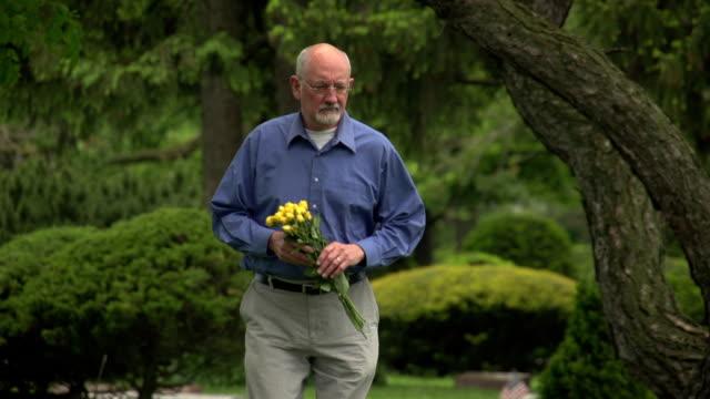 Older man walking through cemetery holding flowers video