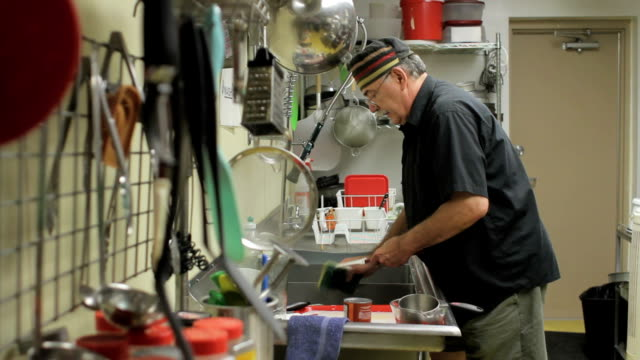 Older man washing dishes in a restaurant kitchen Older man washing dishes in a restaurant kitchen washing dishes stock videos & royalty-free footage