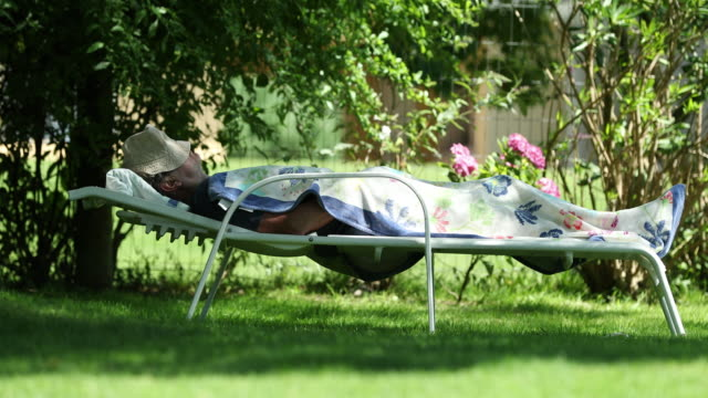 older retired man asleep under a tree during summer day - sonnecchiare video stock e b–roll