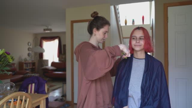 vidéos et rushes de soeur aînée coupant les cheveux de sa sœur cadette à la maison, et les deux d'entre eux s'amuser. - salons et coiffeurs