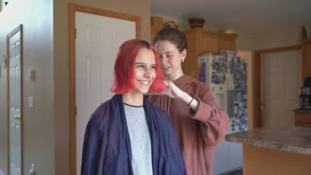 vídeos de stock e filmes b-roll de older sister cutting her younger sister's hair at home, and both of them having fun. - covid hair