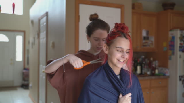 Older sister cutting her younger sister's hair at home, and both of them having fun. Older sister cutting her younger sister's hair at home during a stay at home situation because of the quarantine caused by COVID-19 pandemic. 4K UHD video footage hairstyle stock videos & royalty-free footage