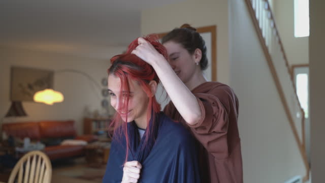 Older sister cutting her younger sister's hair at home, and both of them having fun. - vídeo