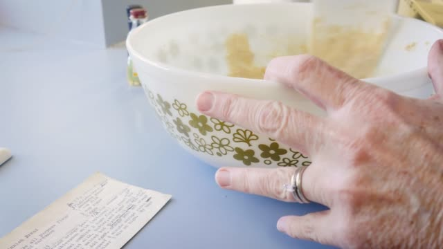 vidéos et rushes de ancienne femme baker remue la pâte dans un millésime bol en 4k - recette
