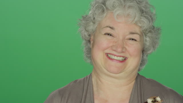 Older woman smiling, on a green screen studio background video