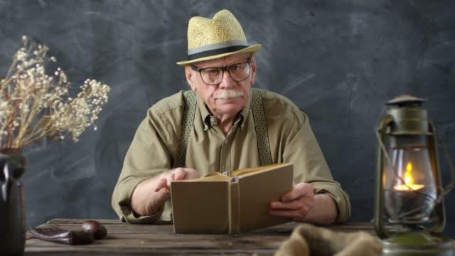 altmodierte ältere mann, die sich in das buch einreidet - strohhut stock-videos und b-roll-filmmaterial