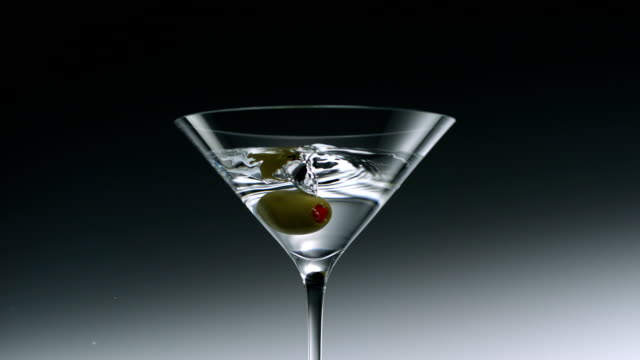 verde oliva cadere nel bicchiere da martini, rallentatore - martini video stock e b–roll