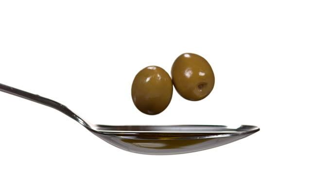 stockvideo's en b-roll-footage met olive vallen voor olijfolie tegen witte achtergrond, slow motion 4k - olijf