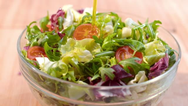 slo mo ld olio di oliva viene versato sopra insalata fresca - olio d'oliva video stock e b–roll