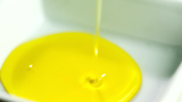 HD Olive oil falling in square bowl video