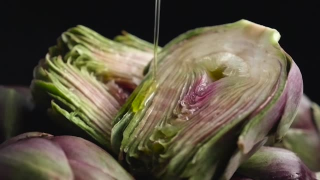 olive oil pouring on sliced artichoke - video