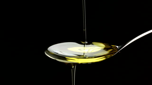 Olive oil pouring on spoon over black background video
