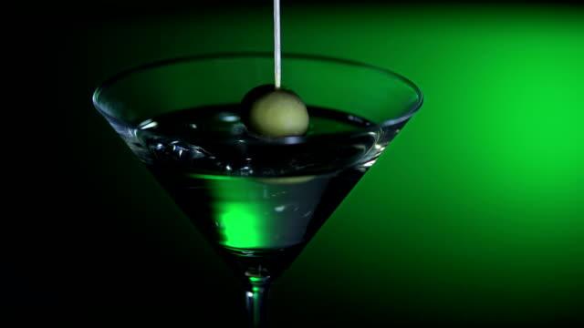 oliva schizzare in un cocktail (super rallentatore) - martini video stock e b–roll