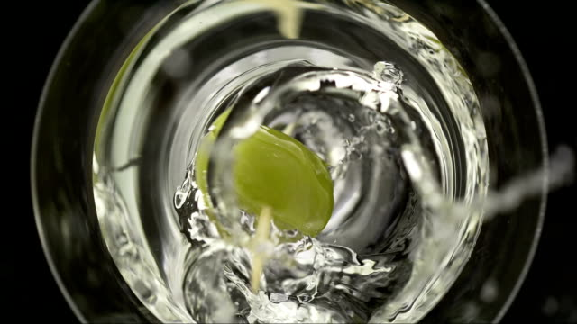 olive splashing into the glass (super slow motion) - martiniglas bildbanksvideor och videomaterial från bakom kulisserna