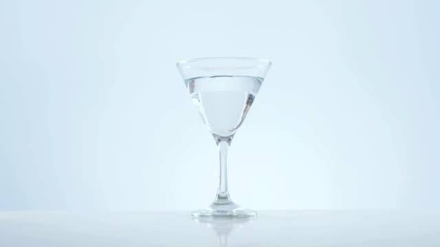 stockvideo's en b-roll-footage met olive stick vallen in cocktailglas - martiniglas