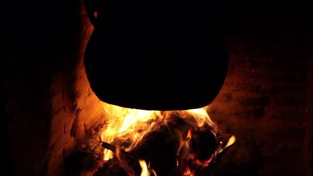 olla negra guisando al calor de una chimenea con leños ardiendo - Vidéo