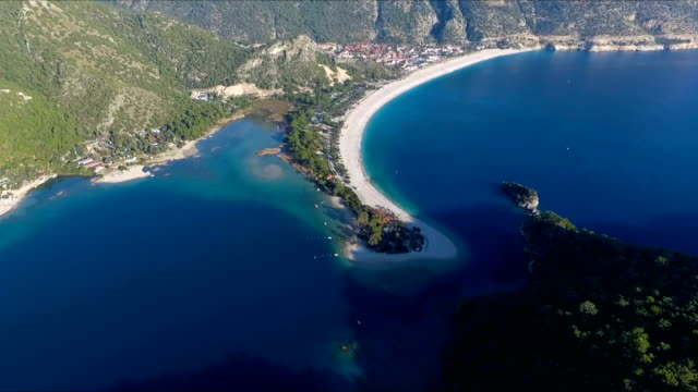 Oludeniz Turkey Ölüdeniz (literally Dead Sea, due to its calm waters even during storms; official translation name Blue Lagoon) is a small village and beach resort in the Fethiye district of Muğla Province, on the Turquoise Coast of southwestern Turkey, at the conjunction point of the Aegean and Mediterranean seas. It is located 14 km (9 mi) to the south of Fethiye, near Mount Babadağ. aegean turkey stock videos & royalty-free footage