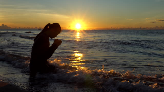 oman praying on beautiful sunset background - modlić się filmów i materiałów b-roll