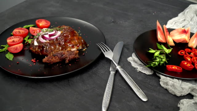 On a black plate lies a beef with sauce and onion, sliced tomatoes with basil are laid out, a sliced tomato and peach are on the next plate, next to it there is a rosemary branch. Between them is a knife and fork video