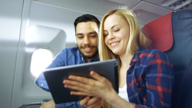 on a board of commercial airplane beautiful young blonde with handsome hispanic male use tablet computer and smile. sun shines through aeroplane window. - estonia filmów i materiałów b-roll