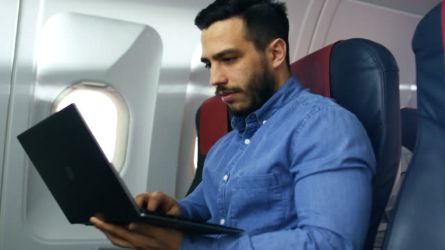 On a Board of Commercial Airplane  Handsome Hispanic Male Works on His Laptop. Sun Shines Through Aeroplane Window.