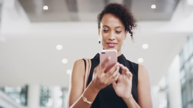 On a corporate quest to connect 4k video footage of a young businesswoman using a smartphone while walking through a modern office african american ethnicity stock videos & royalty-free footage
