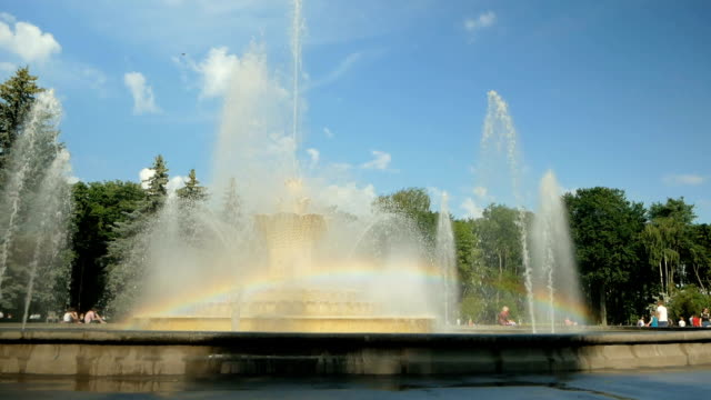 On a large fountain in the park a beautiful rainbow formed. Water hits up