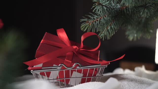 on a pile of snow under the tree, one hand in a mitten put a shopping basket and a red box with a gift is thrown into it