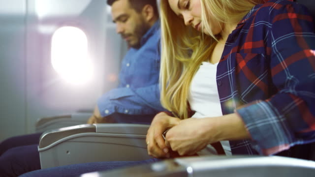 On a Plane Beautiful Blonde Female and Handsome Hispanic Male Fasten They're Seat Belts and Ready to Take off/ Landing. Sun Shines Through Airplane's Window. video
