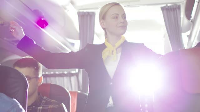 비행기에 아름 다운 스튜 어디 스/승무원이 보여줍니다 안전 조치 지침 및 비상구 루틴. - 안전 스톡 비디오 및 b-롤 화면