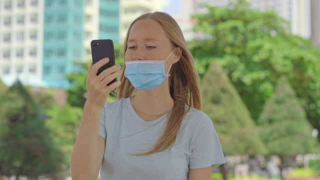 On a street a young woman talks to a phone wearing medical face mask in the wrong way. Her mask does not cover her nose. Wrong-way of using a face mask