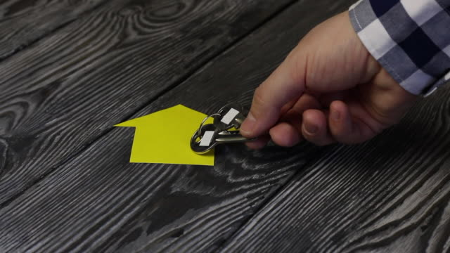 on a table made of brushed boards lies the silhouette of a house cut out of paper. a man puts a bunch of keys on him. taken in detail. - key ring stock videos & royalty-free footage