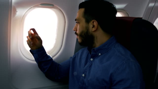 On a Transatlantic Flight Young Hispanic Male Opens Shade and Looks out of the Window. video