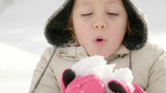 på en vinter dag, en vacker flicka i bergen spelar för att kasta snön i luften och titta på det faller. - snow kids bildbanksvideor och videomaterial från bakom kulisserna