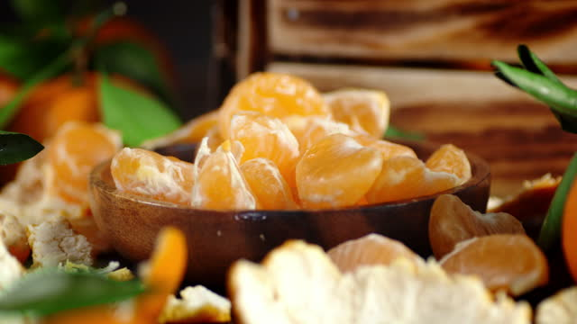 On a wooden plate falling slices of Mandarin.